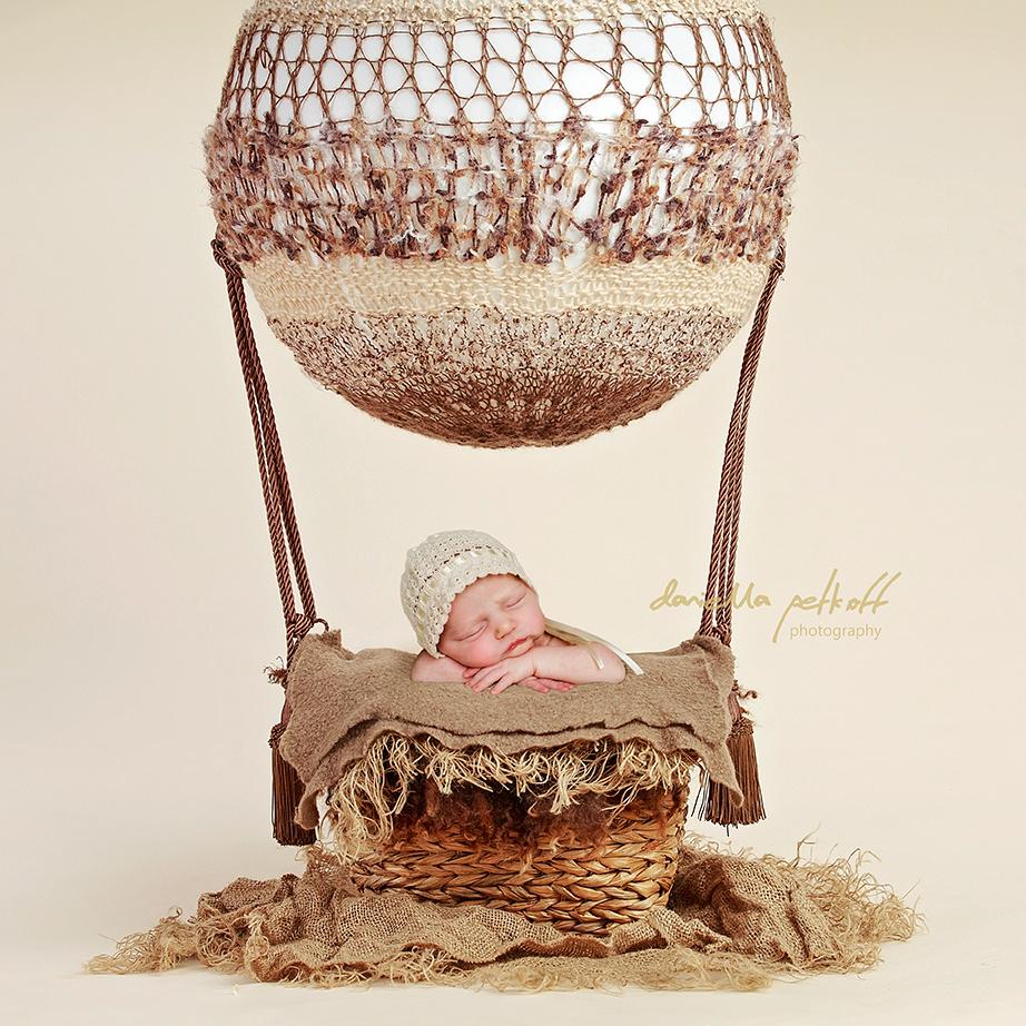Digital Composition of Newborn Baby wearing a bonnet asleep in a hot air balloon