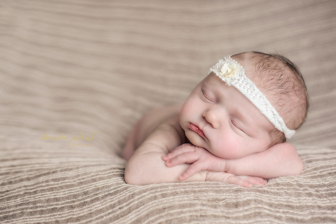 Newborn baby girl sleeping on a stripey blanket with a pretty white headband on.