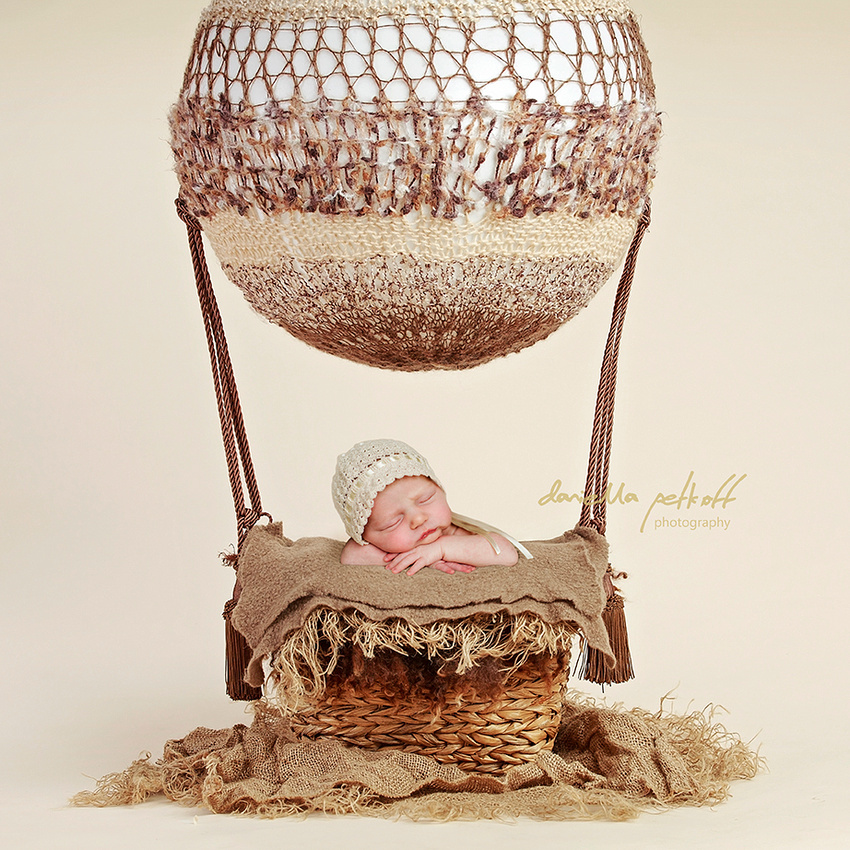 Digital Composition of Newborn Baby wearing a bonnet asleep in a hot air balloon