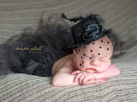Newborn baby girl sleeping in Gatsby style outfit